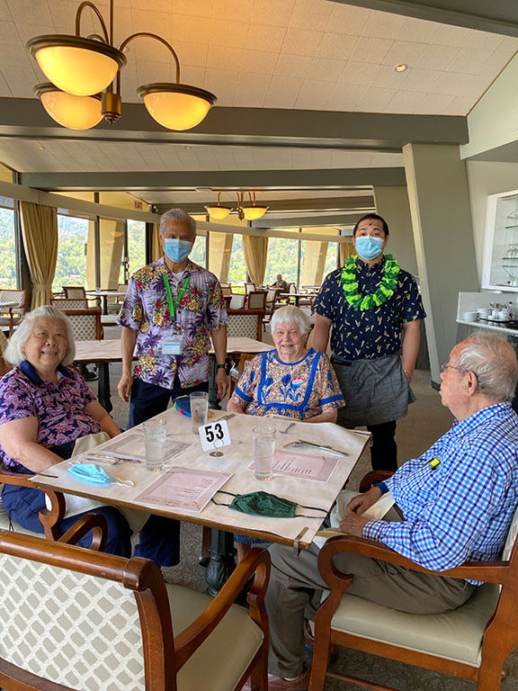 Three Tamalpais residents wearing Hawaiian attire are seated at a table with two masked staff standing nearby