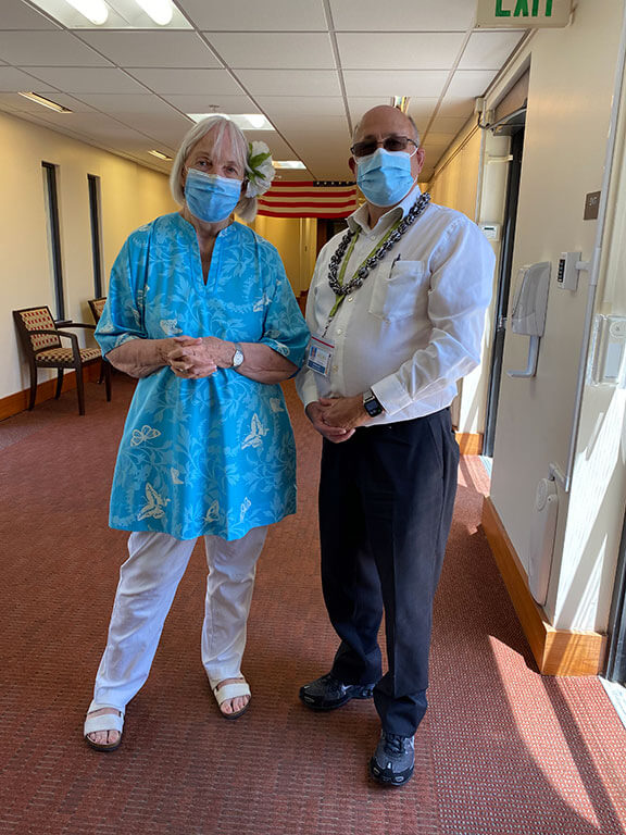Two people wearing Hawaiian clothes and accessories stand in a hallway at The Tamalpais